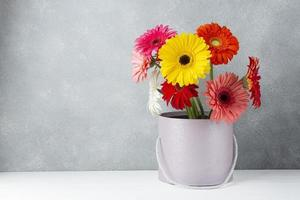 Anordnung von Gerbera-Gänseblümchenblumen in einem Eimer foto
