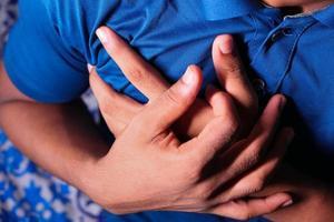 Person, die Brust umklammert und einen Herzinfarkt erleidet foto