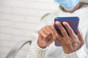 reife Frau, die ein Smartphone beim Tragen einer Maske hält foto