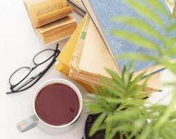Bücherarrangement mit Tasse und Gläsern foto