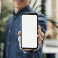 Geschäftsmann zeigt Telefon mit leerem Bildschirm foto