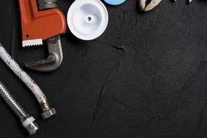 verschiedene Werkzeuge und Rohre auf schwarzem Hintergrund foto