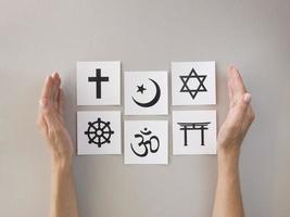 Flache Auswahl religiöser Symbole, die von Händen eingefasst sind foto