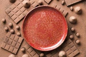 flaches Sortiment mit Schokolade und roter Keramikplatte foto