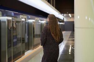 Ein Mädchen in einer chirurgischen Gesichtsmaske hält soziale Distanz zu einer U-Bahnstation foto