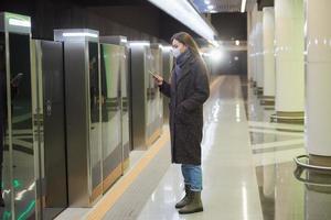 Eine Frau in einer medizinischen Gesichtsmaske wartet auf einen ankommenden Zug in der U-Bahn foto