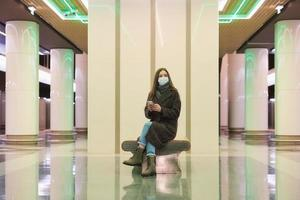 Eine Frau in einer medizinischen Gesichtsmaske wartet auf einen Zug und hält ein Smartphone in der Hand foto