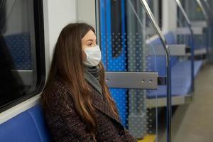 Eine Frau in einer medizinischen Gesichtsmaske hält in einem modernen U-Bahnwagen soziale Distanz foto