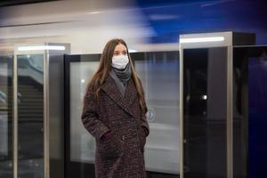 Frau in einer medizinischen Gesichtsmaske steht in der Nähe des abfahrenden Zuges in der U-Bahn foto