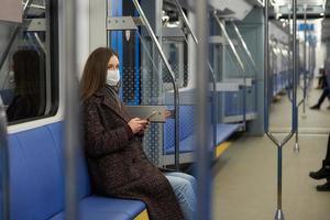Eine Frau in einer Gesichtsmaske sitzt und benutzt ein Smartphone in einem modernen U-Bahn-Wagen foto