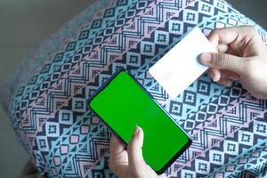 Frau, die ein Telefon- und Visitenkartenmodell hält foto