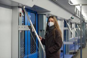 Eine Frau in einer Gesichtsmaske steht und benutzt ein Smartphone in einem modernen U-Bahn-Wagen foto