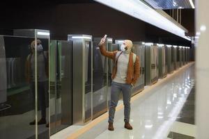 Ein Mann in einer Gesichtsmaske benutzt ein Smartphone, während er auf eine U-Bahn wartet foto