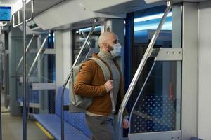 Ein kahlköpfiger Mann mit Bart in einer Gesichtsmaske verlässt ein U-Bahn-Auto foto