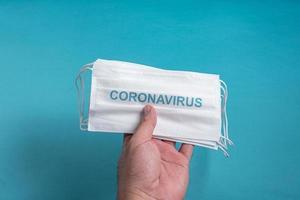 Hand des Mannes, die eine chirurgische Maske des Koronavirus hält foto