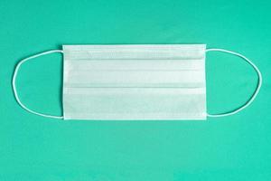 chirurgische Maske über minimalistischem grünem Hintergrund foto