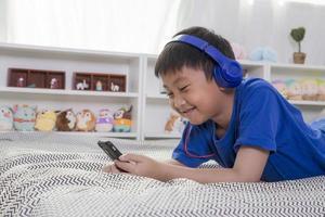 junger asiatischer Junge in den blauen Kopfhörern, die zu Hause lächeln und Musik hören foto