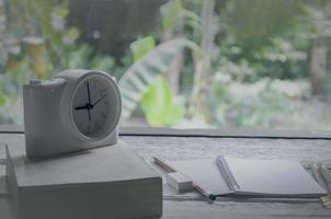 Weinleseklassenzimmer im Naturhintergrund mit Notizbuch, Stiften und Wecker foto