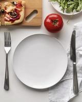 Pizza und Tomate und leerer weißer Teller foto