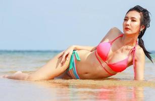 schöne asiatische Frau, die am Strand faulenzt foto