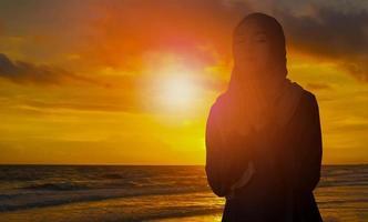 Silhouette der jungen muslimischen Frau in einem schwarzen Hijab foto