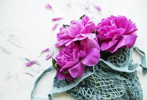 Netztasche mit Pfingstrosenblüten foto