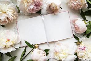 Pfingstrosenblumen und leeres Notizbuch foto