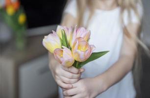 Frühlingstulpen in den Händen eines kleinen Mädchens. foto