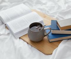 Lesen im Bett mit Kaffee foto