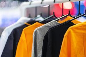 Nahaufnahme von T-Shirts auf Kleiderbügeln, Bekleidungshintergrund foto