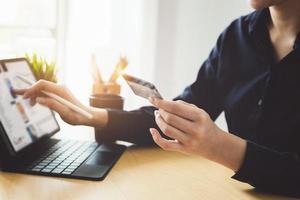 Frau, die online auf einem Tablet zahlt foto
