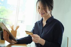 Frau zahlt auf ihrem Tablet foto
