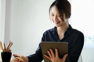 Frau mit Tablet zu bezahlen foto