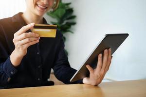 Frau, die eine Tablette und eine Kreditkarte hält foto