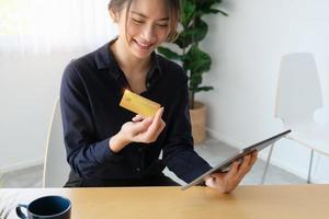 Frau, die eine Kreditkarte betrachtet und eine Tablette hält foto