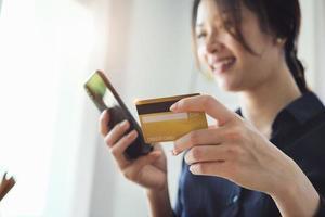 Frau, die Kreditkarteninformationen auf ihrem Telefon eingibt foto