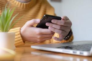 junge asiatische Frau, die sich von den sozialen Medien trennt und ihr Smartphone ausschaltet. digitales Entgiftungskonzept. foto