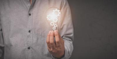 Die Hand eines Geschäftsmannes hält eine Glühbirne und hat ein Zahnradsymbol foto