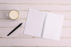 Notizbuch und ein Glas Milch auf dem Schreibtisch foto