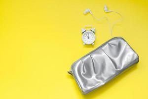 silberne Kosmetiktasche, Wecker und Kopfhörer auf gelbem Hintergrund foto