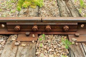Nahaufnahme der Eisenbahnschienenverbindung mit rostigen Schrauben foto