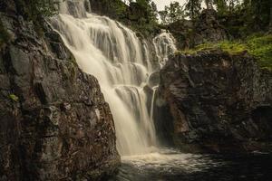 Wasserfall läuft einen Berghang in Nordschweden hinunter foto