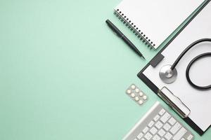 Stethoskop- und Blisterpackungspillen mit Büromaterial auf grünem Hintergrund foto