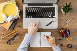 Student, der in Notizbuch mit Computer am Schreibtisch schreibt foto