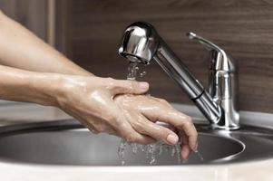 Frau, die Hände im Waschbecken wäscht foto