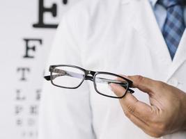 männlicher Arzt hält eine Brille in den Händen foto