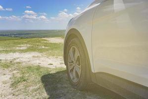 Teil eines weißen Geländewagens mit einem Rad auf einem natürlichen Landschaftshintergrund. foto
