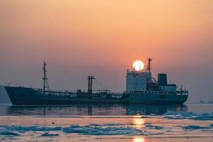 Seestück mit Fischerboot auf Sonnenunterganghintergrund. foto