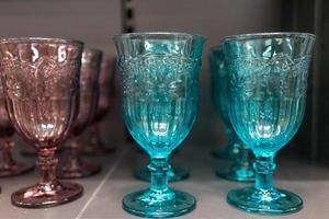 hohe geformte Gläser aus farbigem Glas, die auf einem Regal stehen. foto