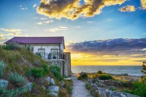 kleines Haus am Meer während des Sonnenuntergangs foto
